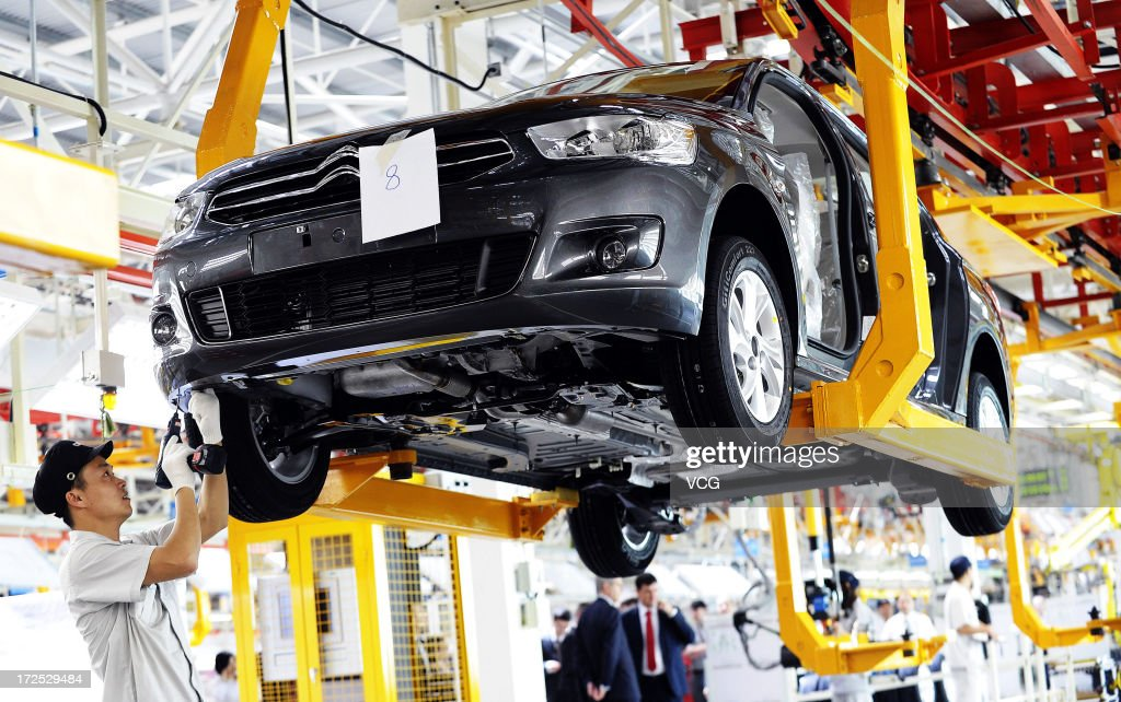 Employees work on the assembly line of the Citroen C-Elysee at the third plant of Dongfeng Peugeot Citroen Automobile Co., Ltd (DPCA) on July 2, 2013 in Wuhan, China. The third plant of DPCA, a joint venture between the French automaker PSA Peugeot Citroen and the Chinese automaker Dongfeng Motor Corp., was put into operation on Tuesday, with initial capacity of 150,000 cars a year.