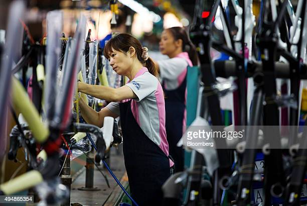 Employees work on the assembly line of the Giant Manufacturing Co bicycle manufacturing facility in Taichung Taiwan on Thursday Oct 22 2015 King Liu...