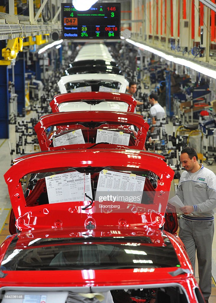 Employees work on the assembly of new Fiat 500L automobiles on the production line at the Fiat Automobili Srbija plant in Kragujevac, Serbia, on Wednesday, March 20, 2013. Fiat Automobili Srbija, a joint venture between the government and Italian carmaker Fiat, is Serbia's sole automaker. Photographer: Oliver Bunic/Bloomberg via Getty Images