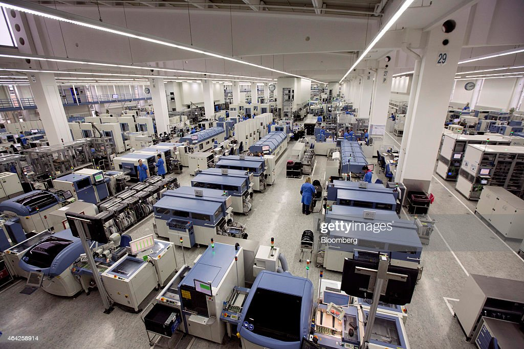 Employees work on the automated assembly line at the Siemens AG electronics factory in Amberg Germany on Monday Feb 23 2015 German business...