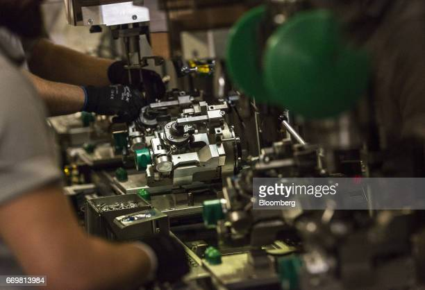 Employees work on the automobile diesel engine common rail pump production line at the Robert Bosch GmbH digital factory in Stuttgart Germany on...