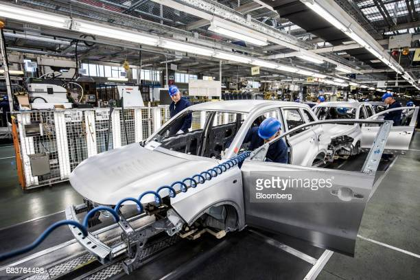 Employees work on the body shell of an automobile on the production line inside the Suzuki Motor Corp plant in Esztergom Hungary on Monday May 15...