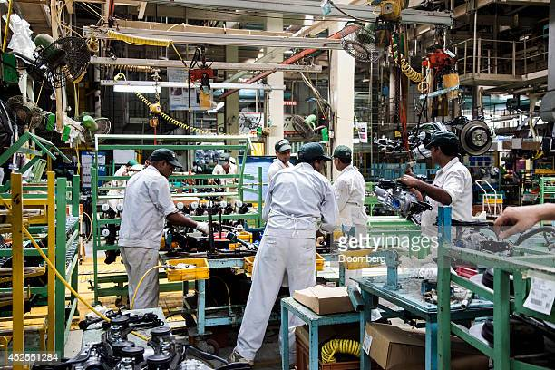 Employees work on the brake pads of Honda Motor Co Mobilio vehicles on the production line at the Honda Cars India Ltd plant in Greater Noida India...