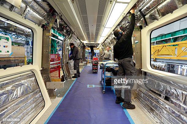 Employees work on the interior of a London Underground subway carriage at Bombardier Inc's Litchurch Lane railcar factory in Derby UK on Tuesday Feb...