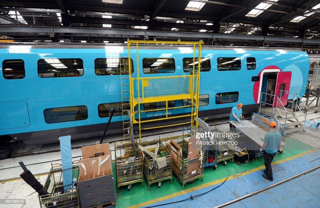 Employees work on the new low-cost TGV high-speed train 'Ouigo' at the assembling plant in Bischheim, eastern France, on February 19, 2013. France's state rail firm SNCF opened its online booking service for its new budget train service 'Ouigo' on February 19 inspired by the budget airline model. The train will start transporting its first passengers from April 2, with the Ouigo service operating from Marne-la-Vallée near Disneyland Paris, Lyon-Saint-Exupéry airport, Marseilles and Montpellier. AFP PHOTO / PATRICK HERTZOG