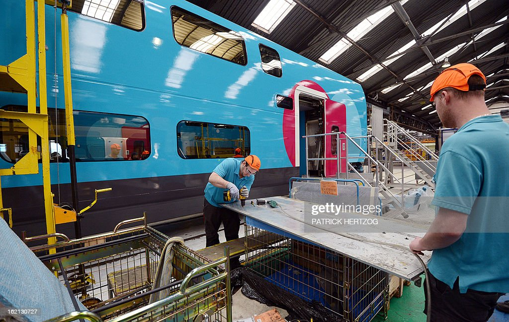 Employees work on the new low-cost TGV high-speed train 'Ouigo' at the assembling plant in Bischheim, eastern France, on February 19, 2013. France's state rail firm SNCF opened its online booking service for its new budget train service 'Ouigo' on February 19 inspired by the budget airline model. The train will start transporting its first passengers from April 2, with the Ouigo service operating from Marne-la-Vallée near Disneyland Paris, Lyon-Saint-Exupéry airport, Marseilles and Montpellier.