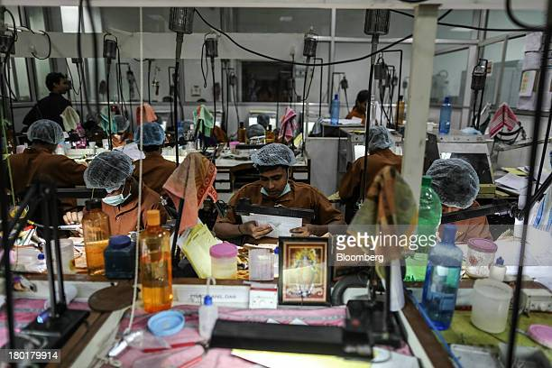 Employees work on the production line inside the diamond studded gold and platinum manufacturing facility at Kama Schachter Jewelry Pvt Ltd in Mumbai...