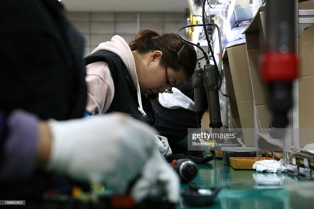 Employees work on the production line manufacturing cordless drills at the Aimsak Corp. factory during a media tour organized by Korea Industrial Complex Corp. (KICOX) in Cheongwon, South Korea, on Friday, Nov. 23, 2012. KICOX, which develops and manages industrial complexes and support for resident enterprises as a public company under South Korea's Ministry of Knowledge Economy, held a media tour to the plant. Photographer: SeongJoon Cho/Bloomberg via Getty Images