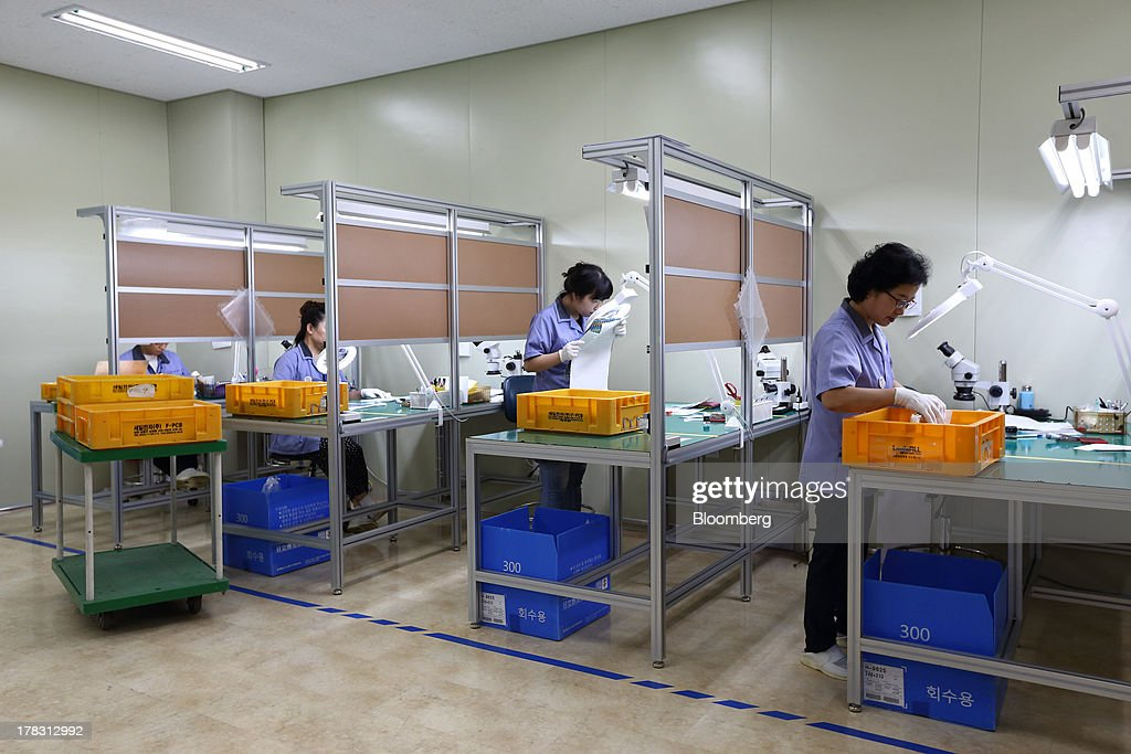 Employees work on the production line manufacturing Flexible Printed Circuit Boards (F-PCB) at the Seil Electronics Co. factory in Incheon, South Korea, on Wednesday, Aug. 28, 2013. South Korea has surpassed Brazil, Russia and India to become the second-biggest emerging stock market for the first time since 2006, as a stable won and record current-account surplus lure investors. Photographer: SeongJoon Cho/Bloomberg via Getty Images