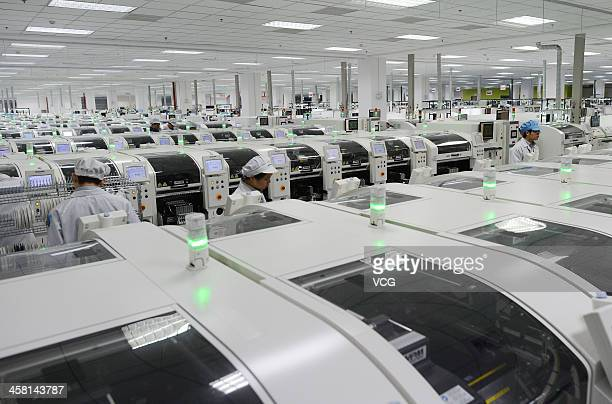 Employees work on the production line of smart phone at the Lenovo MIDH Wuhan Operation Center on December 19 2013 in Wuhan China The plant will...