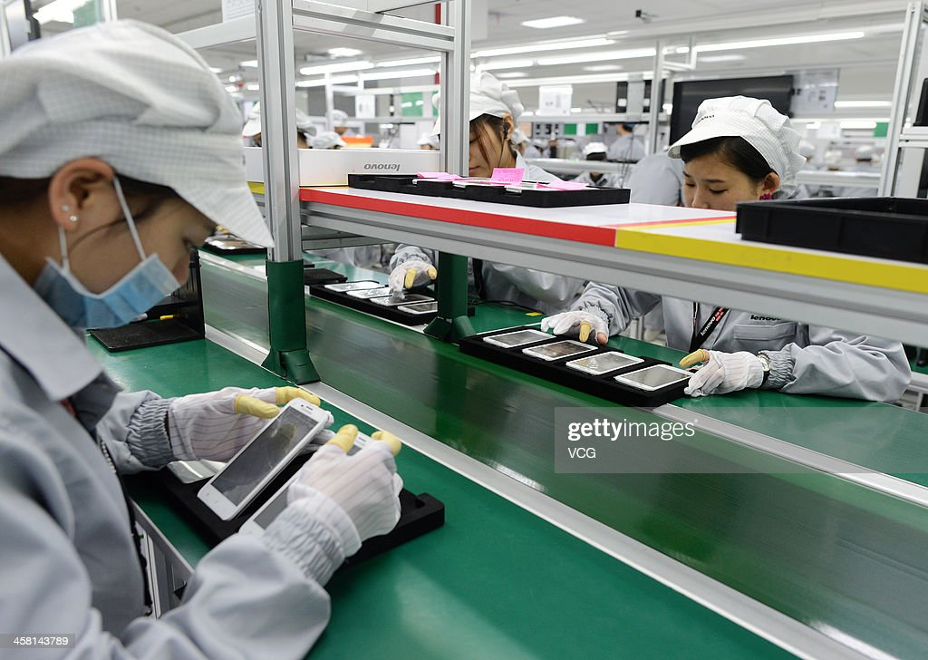 Employees work on the production line of smart phone at the Lenovo MIDH (Mobile Internet and Digital Home) Wuhan Operation Center on December 19, 2013 in Wuhan, China. The plant will mainly produce Lenovo smart phones and tablet computers with an initial capacity of 30 million units a year.