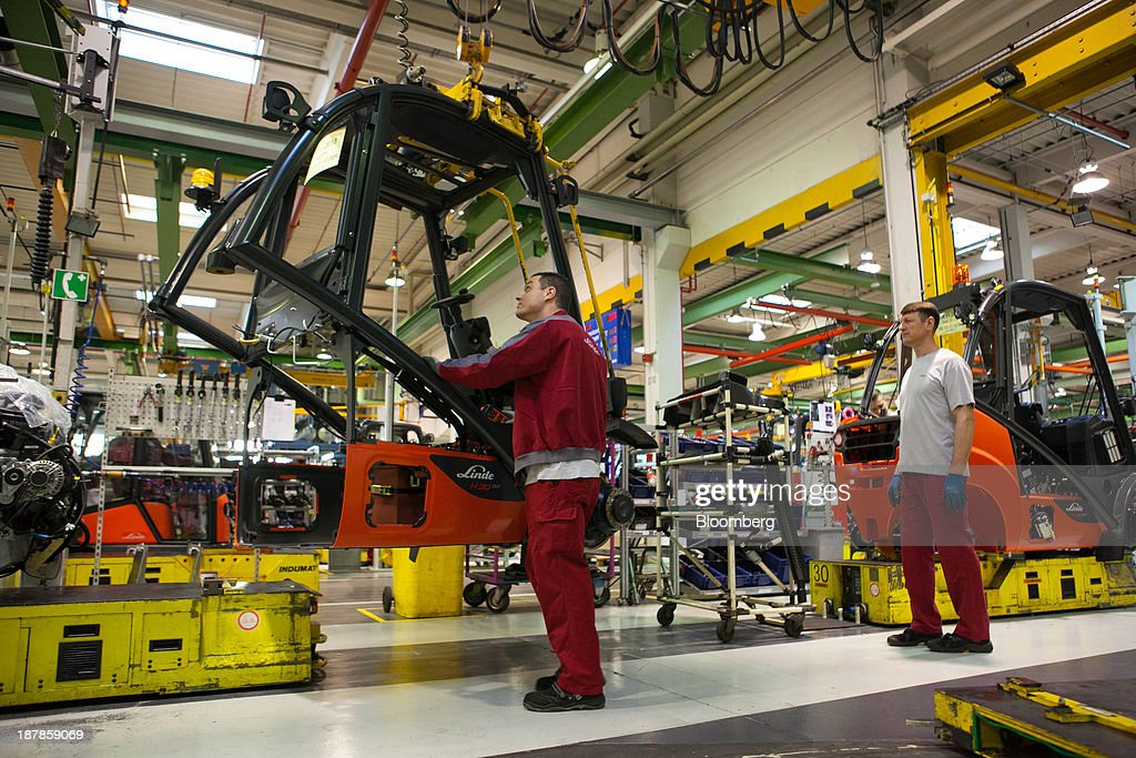 Employees work on the production of Linde H30 forklift trucks as its sits on the production line at the Linde Material Handling GmbH factory, a unit of Kion Group AG, in Aschaffenburg, Germany, on Tuesday, Nov. 12, 2013. Kion Group AG, the German forklift-maker which listed shares in June, is looking to expand its global sales network via acquisitions to catch up with main competitor Toyota Industries Corp. Photographer: Krisztian Bocsi/Bloomberg via Getty Images