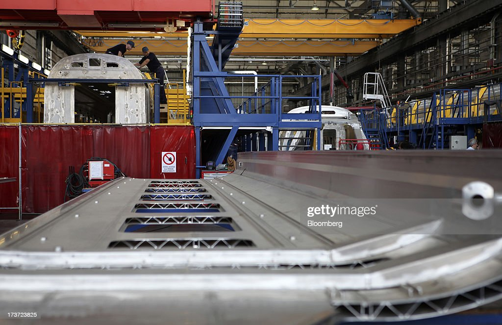 Employees work on the roof section of a Frecciarossa 1000 high-speed train carriage during manufacture at AnsaldoBreda SpA's rail-car plant in Pistoia, Italy, on Tuesday, July 16, 2013. Italian business confidence rose last month after Prime Minister Enrico Letta's Cabinet passed plans to boost employment and postponed the payment of the value-added tax planned for July. Photographer: Alessia Pierdomenico/Bloomberg via Getty Images