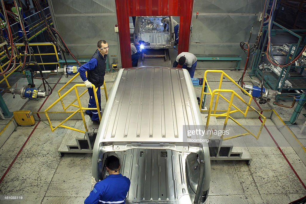Employees work on the shell of a Ford Connect van as it travels along the production line at the Ford Otosan plant, the joint venture between Ford Motor Co.'s Ford Otomotiv Sanayi AS and Koc Holding AS, in Golcuk, Turkey, on Wednesday, Nov. 20, 2013. Istanbul-based Automobile Distributors' Association, or ODD, forecasts Turkey's total automotive industry market to be between 830k and 870k this year. Photographer: Kerem Uzel/Bloomberg via Getty Images