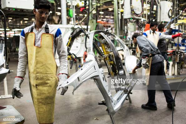 Employees work on the side frame of a Volkswagen AG Vento automobile on the production line at the Volkswagen India Pvt plant in Chakan Maharashtra...