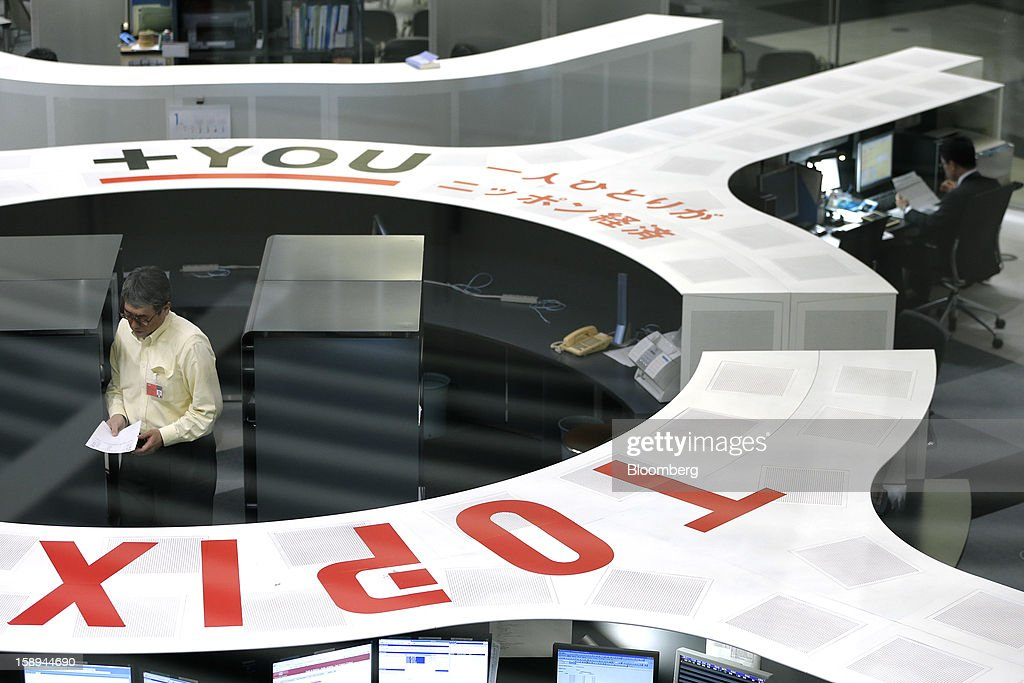 Employees work on the trading floor of Japan Exchange Group Inc.'s Tokyo Stock Exchange (TSE) on the first trading day of the year in Tokyo, Japan, on Friday, Jan. 4, 2013. Japan Exchange, created by the merger of Japan's two biggest bourses, fell in its trading debut on the Tokyo Stock Exchange. Photographer: Kiyoshi Ota/Bloomberg via Getty Images