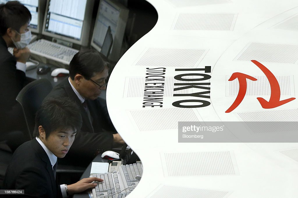 Employees work on the trading floor of the Tokyo Stock Exchange (TSE) on the last trading day of the year in Tokyo, Japan, on Friday, Dec. 28, 2012. Japanese stocks rose, with the Nikkei 225 Stock Average capping its biggest yearly advance since 2005, as the yen weakened after consumer prices and industrial production data fueled speculation the central bank will respond to calls for more stimulus. Photographer: Kiyoshi Ota/Bloomberg via Getty Images