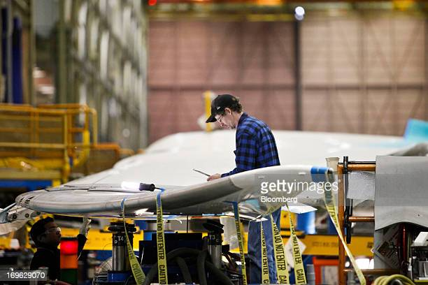 Employees work on the wing of a Boeing Co 787 Dreamliner during final assembly of the airplane at the Boeing Co factory in Everett Washington US on...
