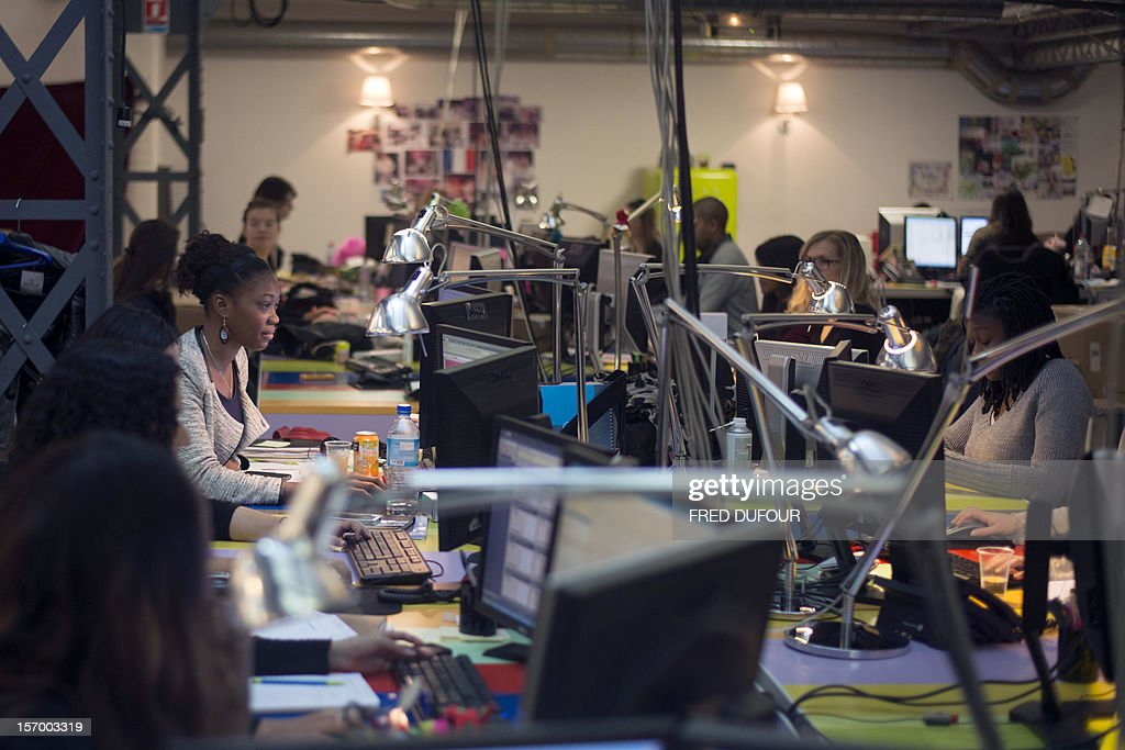 Employees work on their computers at the headquarters of vente-privee.com, in Saint-Denis, north of Paris, on November 27, 2012, ahead of the Christmas and new Year celebrations. The vente-privee.com storage facilities celebrates its 10th anniversary. AFP PHOTO / FRED DUFOUR