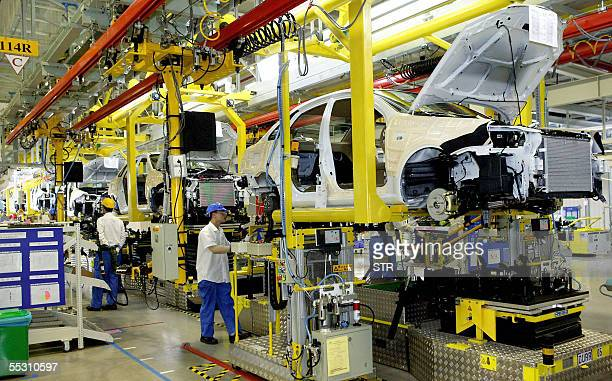 Employees work on various models of General Motors cars at a plant in Shanghai 07 September 2005 US auto giant GM is snapping at the heels of China's...