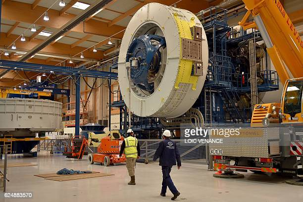 Employees work to build an offshore wind turbine on November 21 2017 in MontoirdeBretagne western France at a factory of US company General Electric...
