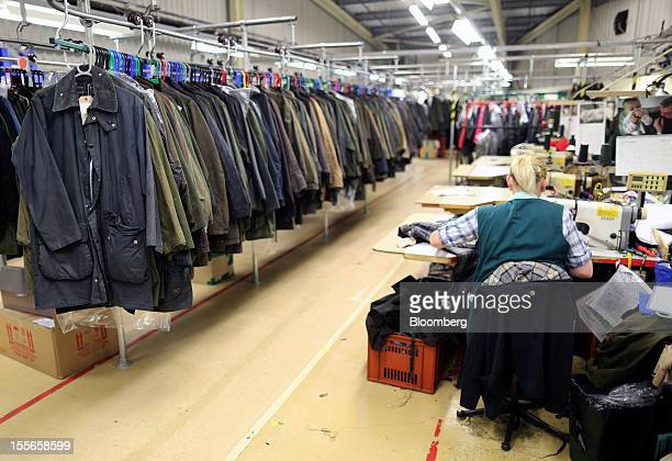 Employees work to repair customers' Barbour jackets at the headquarters of J Barbour Sons Ltd in South Shields UK on Tuesday Nov 6 2012 While the UK...