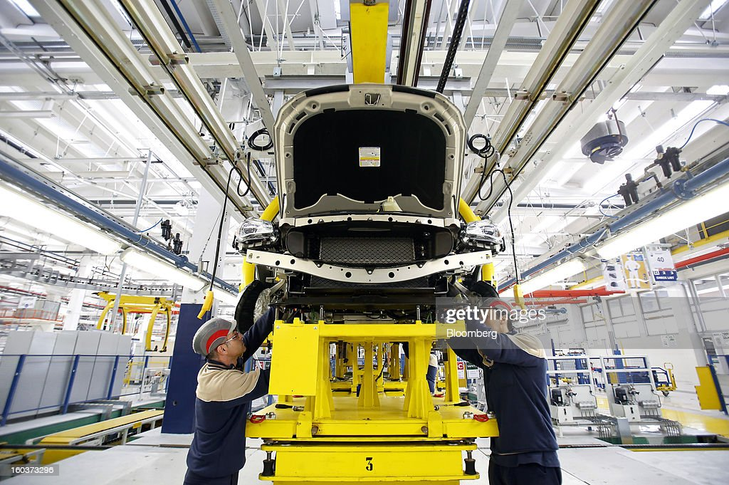 Employees work under the wheel arches of a Maserati Quattroporte luxury automobile as it travels along the production line at Fiat SpA's Grugliasco factory in Turin, Italy, on Wednesday, Jan. 30, 2013. Fiat SpA Chief Executive Officer Sergio Marchionne said the Italian carmaker narrowed losses in Europe in the fourth quarter, helping it achieve full-year earnings that were in line with its forecasts. Photographer: Alessia Pierdomenico/Bloomberg via Getty Images