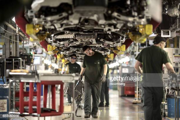 Employees work underneath Jaguar automobiles on the final assembly line at Tata Motors Ltd's Jaguar assembly plant in Castle Bromwich UK on Thursday...