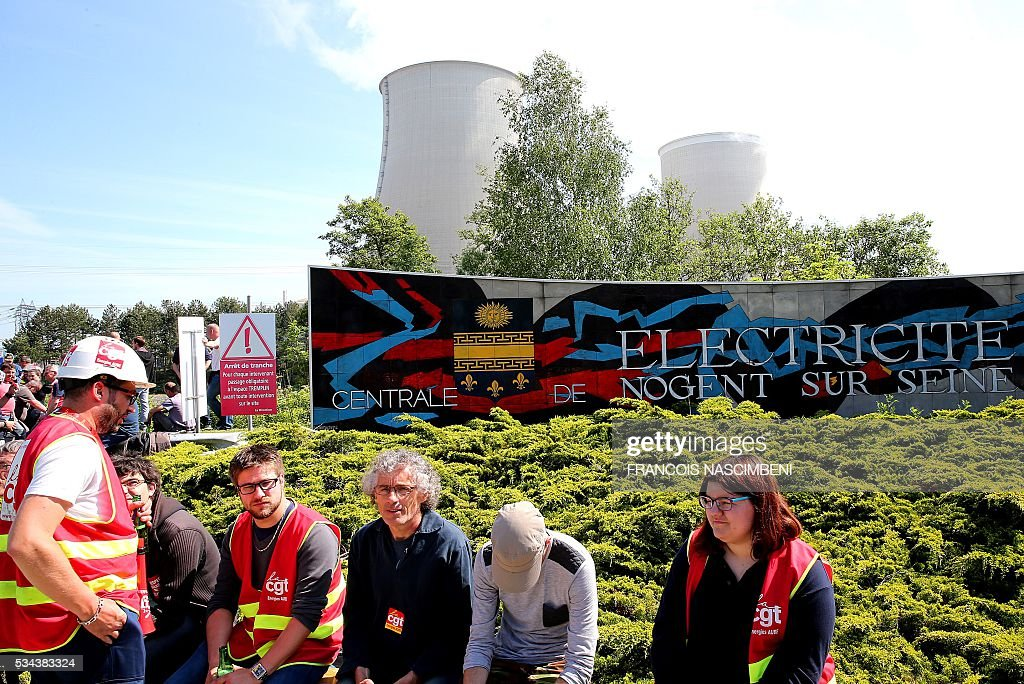Employess and unionists rally outside the Nogent nuclear power plant at Nogent-sur-Marne, east of Paris on May 26, 2016, during a protest against controversial labour market reforms that has already severely disrupted fuel supplies. With two weeks until France hosts the Euro 2016 football championships, the country has been paralysed by a series of transport strikes and fuel shortages that has heaped pressure on the deeply unpopular Socialist government. / AFP / FRANCOIS