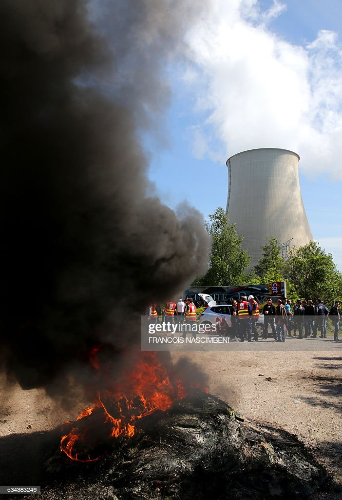 Employess and unionists rally outside the nuclear power plant of Nogent-sur-Marne, an eastern suburbs of Paris on May 26, 2016, during a protest against controversial labour market reforms that has already severely disrupted fuel supplies. With two weeks until France hosts the Euro 2016 football championships, the country has been paralysed by a series of transport strikes and fuel shortages that has heaped pressure on the deeply unpopular Socialist government. / AFP / FRANCOIS