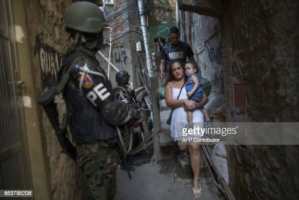 TOPSHOT Employing urban combat tactics Brazilian army military police personnel patrol along an alley in the Rocinha favela in Rio de Janeiro Brazil...