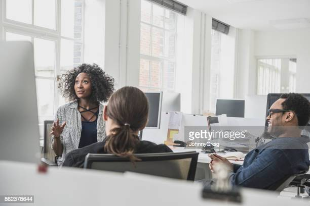 Empowered African businesswoman explaining to two male colleagues and looking at computer