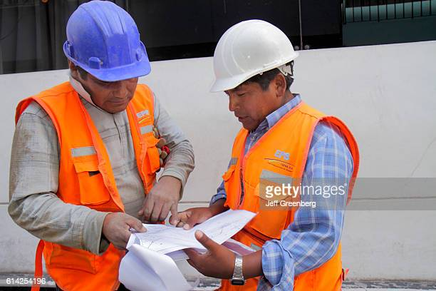 Empresa Publica de Saneamiento EPS public works workers examining specs on blueprint