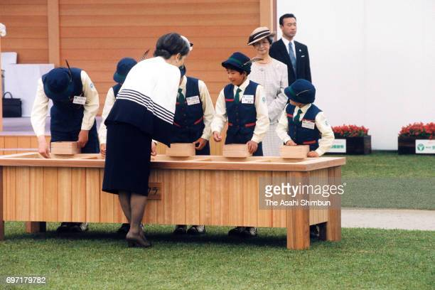 Empress Michiko casts seed with children during the 46th National Tree Planting Festival at the Central Forest Park on May 21 1995 in Hongo Hiroshima...
