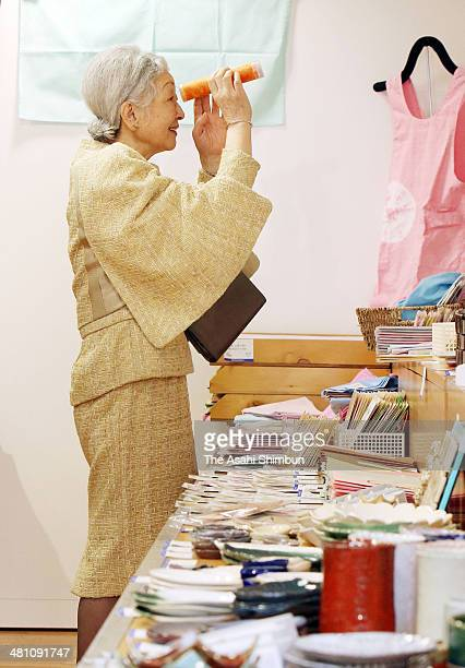 Empress Michiko looks into a kaleidoscope during the exhibition of the Asahide Specialized School which is for mentally deficient children at...