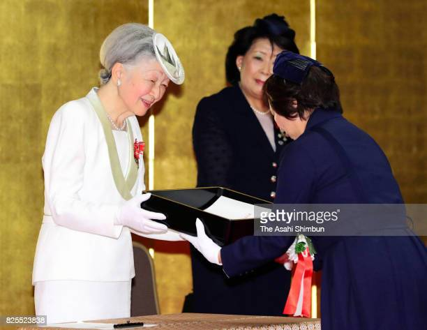 Empress Michiko presents the certificate to a laureate during the Florence Nightingale Medal Ceremony on August 2 2017 in Tokyo Japan