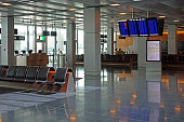 Empty airport departure lounge waiting area with flight information screens.