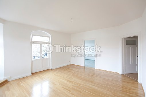 Empty All White Living Room In A Loft With Tan Wooden Floors Stock Photo