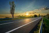 Empty asphalt road around farm fields in rural landscape at sunset
