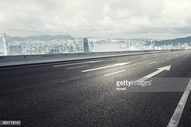 empty asphalt road over through modern city  in cloudy sky