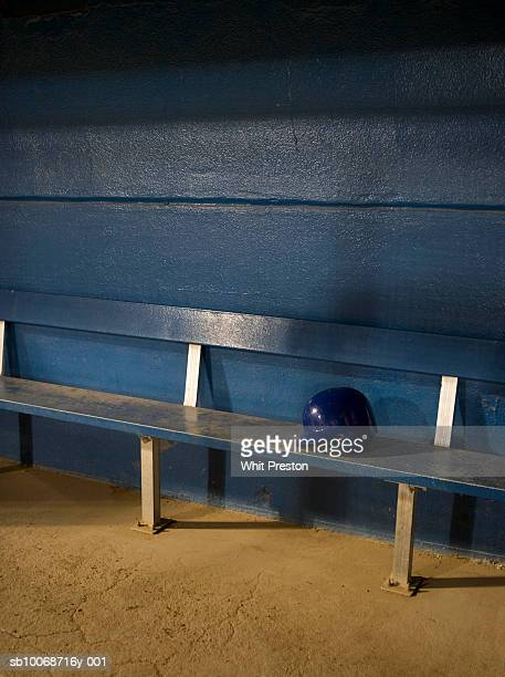 Empty baseball dugout with helmet