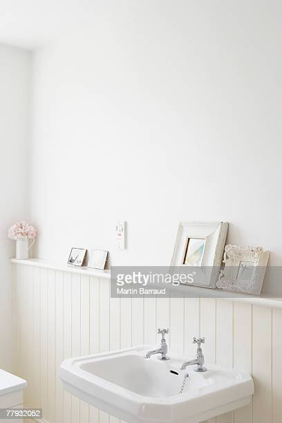 Empty bathroom with pictures on shelf