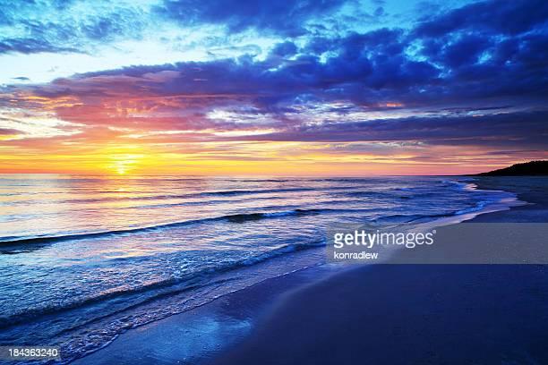 空のビーチと海に沈む夕日