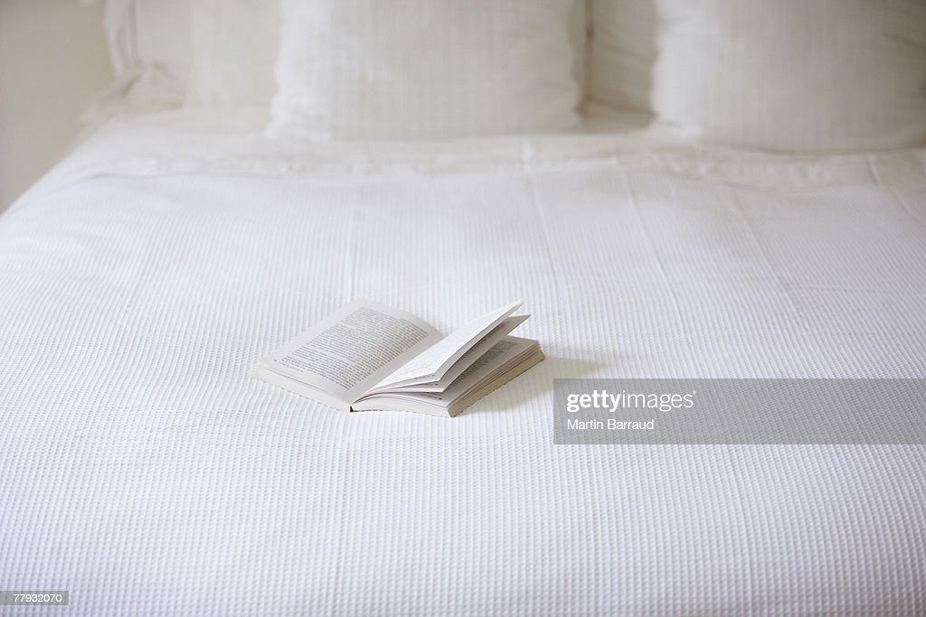 Empty bed with open book on it : Stock Photo