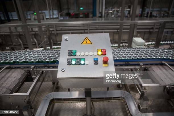 Empty beer cans moving along a conveyor pass a control panel at the Heineken NV brewery in Yangon Myanmar on June 15 2017 Heineken is seeking to...