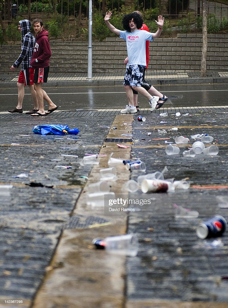 Empty beer cans, plastic glasses and rubbish lie on the street as British students react to the camera after the second night of parties during the SalouFest on April 3, 2012 in Salou, Spain. Saloufest is a university sports tour attended by thousands of British students taking part in a variety of competitions and parties over the Easter period in the Catalan village of Salou.