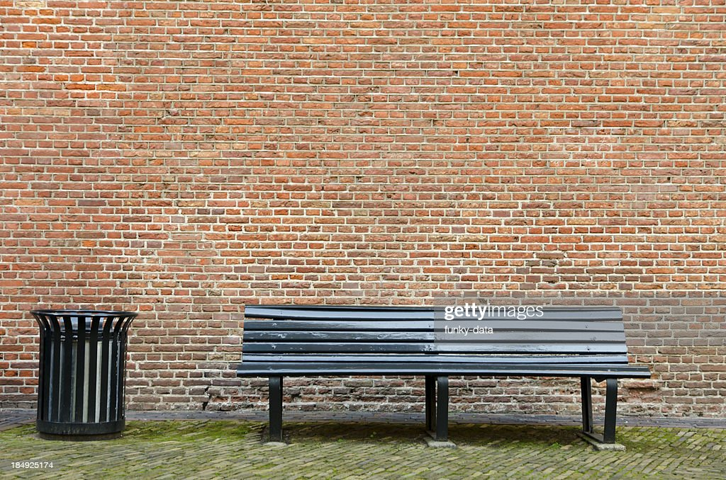 Empty bench and garbage bin
