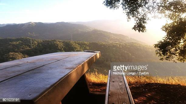 Empty Bench And Table On Field Against Mountains