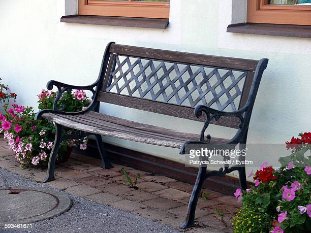 Empty Bench By Flower Pots Outside House