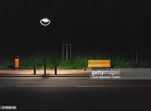 Empty Bench By Illuminated Street Light At Roadside During Night